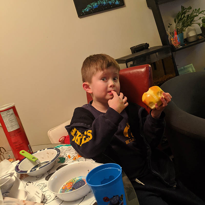 boy steals fruit from bowl